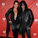 Musician Slash (R) and Perla Hudson attend the MusiCares MAP Fund Benefit Concert at Club Nokia on May 12, 2014 in Los Angeles, California - 410 x 594