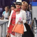Catherine Zeta-Jones arrives at airport in a chic all-white ensemble with her mother and lookalike daughter Carys in tow