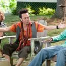Rob Hilliard (Rob Schneider) tells a story to the guys at the Lake House as Marcus Higgins (David Spade) listens and Kurt McKenzie (Chris Rock) laughs at Hilliard's story in Columbia Pictures' GROWN UPS. Photo By: Tracy Bennett. ©2009 Columbia Tri - 454 x 303