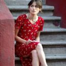 Keira Knightley wears a red floral dress and Adam Levine sports a full beard as they sit on a stoop while filming scenes for 'Can a Song Save Your Life?