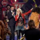 Host Ryan Seacrest, finalist Jax, and singer/songwriter Steven Tyler speak onstage during