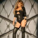 Carmen Electra provocatively poses in lace and leather knee-high boots and plunging gold dress for 2014 calendar
