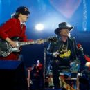 Put your feet up Axl! Rocker Rose puts on belting performance while confined to a chair as he joins AC/DC in Seville with his broken foot still in a cast - 454 x 322
