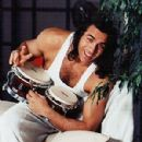 Adrian Paul playing bongo drums