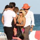 Shauna Sand puts on a pair of tiny pink shorts as she gathers her things and leaves the beach with her husband, Laurent Homburger - 402 x 594