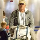 Heavy cargo coming through: Chevy Chase has excess baggage as he wheels both his and wife's luggage through airport
