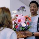 Seen here from left, Karen Mayo Chandler (back to camera) as Maitland Receptionist and Eddie Murphy as Det. Axel Foley - 454 x 256