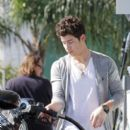 Nick Jonas refuels his Dodge Challenger car at a local gas station in Los Angeles. February 21, 2011