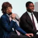 "Mick Jagger and Chadwick Boseman talk prior to a special screening of ""Get On Up"" on September 14, 2014 in London, England"
