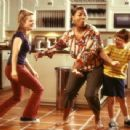 Charlene (Latifah, center) gets down and boogies with Peter's kids, Sarah (Kimberly J. Brown, left) and Georgey (Jones, right)