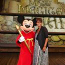 In this handout image provided by Disney Parks, actress Halle Berry meets Mickey Mouse on the stage of the new live musical show, 'Mickey and the Magical Map,' at Disneyland July 22, 2013 in Anaheim, California