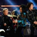 Singer Billy Idol, musicians Steve Stevens and Billy Morrison perform onstage during the first ever iHeart80s Party at The Forum on February 20, 2016 in Inglewood, California. - 454 x 302