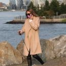 Olivia Palermo – Wearing a white short dress under a coat while out for a walk in Manhattan