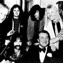 Back row: keyboardist Viv Savage (David Kaff) and drummer Mick Shrimpton (R.J. Parnell) Front row: Spinal Tap manager Ian Faith (Tony Hendra), bass player Derek Smalls (Harry Shearer), president of Polymer Records Sir Denis Eton-Hogg (Patrick MacNee), lea