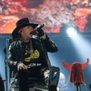 Put your feet up Axl! Rocker Rose puts on belting performance while confined to a chair as he joins AC/DC in Seville with his broken foot still in a cast