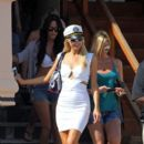 Paris Hilton wears a tight white dress with matching heels and a captains hat as she hosts a July 4th beach party at her Malibu home