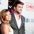 Miley Cyrus and  Liam Hemsworth arrive at the 2012 People's Choice Awards at Nokia Theatre L.A. Live on January 11, 2012 in Los Angeles