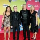 Musician Phil Collen (2nd from left) with wife Anita (L), Joe Elliott (2nd from right) with wife Kristine arrive at the 2006 Billboard Music Awards at the MGM Grand Garden Arena December 4, 2006 in Las Vegas, Nevada. - 454 x 545