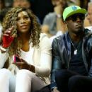 Tennis player Serena Williams (L) and runner Usain Bolt (R) attend Game Four of the 2014 NBA Finals between the Miami Heat and the San Antonio Spurs at American Airlines Arena on June 12, 2014 in Miami, Florida. NOTE TO USER: User expressly acknowledges a - 454 x 331