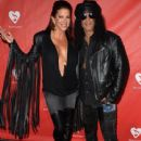 Musician Slash (R) and Perla Hudson attend the MusiCares MAP Fund Benefit Concert at Club Nokia on May 12, 2014 in Los Angeles, California