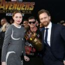 Karen Gillan (L) and Tom Hiddleston (R) post with a fan at the premiere of Disney and Marvel's 'Avengers: Infinity War' on April 23, 2018 in Los Angeles, California. - 454 x 321
