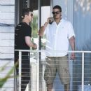 singer Robin Thicke chats with a friend on a balcony while spending New Years Day in Miami, Florida on January 1, 2014