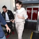 Bella Hadid – Arriving at LAX in a light pink jump suit - 454 x 667