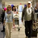Heavy cargo coming through: Chevy Chase has excess baggage as he wheels both his and wife's luggage through airport - 454 x 478