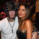 Guitarist Dj Ashba (L) of Guns N Roses and his wife, model Nathalia Henao, attend the UFC 175 event at the Mandalay Bay Events Center on July 5, 2014 in Las Vegas, Nevada - 454 x 584