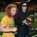 Scott 'Carrot Top' Thompson poses with singer/bassist Gene Simmons of Kiss, owner of the Los Angeles Kiss, as he holds a rivalry trophy before a game against the Las Vegas Outlaws at the Thomas & Mack Center on May 4, 2015 in Las Vegas, Nevada - 435 x 600