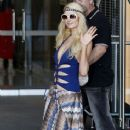 Paris Hilton wears a sarong over a cutout blue one-piece bathing suit as she leaves The Darling Hotel