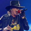 Put your feet up Axl! Rocker Rose puts on belting performance while confined to a chair as he joins AC/DC in Seville with his broken foot still in a cast - 454 x 566