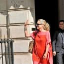 Sharon Stone smiles and wears a loose fitting red and pink dress as she leaves a meeting at Christian Dior