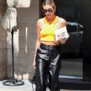 Hailey Baldwin – Wearing an orange tank top and leather pants out in Los Angeles