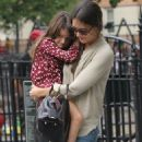 Suri Cruise riding her bike alongside her friend guided by mom Katie Holmes at Bleecker Playground in New York City (August 25)