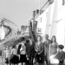 July 29th, 1963 - The Rt Hon Sir David Ormsby-Gore KCMG went aboard the Queen Mary on her arrival today at Southhampton with his children Julian (22, dark glasses), Jane (20) and Victoria (16) to meet his wife Lady Ormsby-Gore, daughter Alice (11, with co - 454 x 426