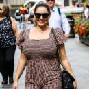 Kelly Brook – In a brown jumpsuit at Heart radio in London