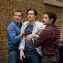"(L-r) Peter (BRADLEY COOPER) holds back Carl (JIM CARREY) with help from Rooney (DANNY MASTERSON) in Warner Bros. Pictures' and Village Roadshow's comedy ""Yes Man,"" distributed by Warner Bros. Pictures. Photo by Melissa Moseley - 454 x 303"