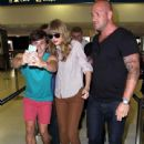 Taylor Swift posing with a fan while her bodyguard stands close by before catching a flight back to Los Angeles in Sydney, Australia on November 30, 2012