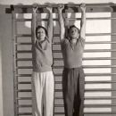 Health Club Owner Terry Hunt, Trainer of Movie Stars, Hanging from Horizontal Bars with Mary Astor
