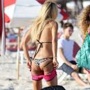 Shauna Sand puts on a pair of tiny pink shorts as she gathers her things and leaves the beach with her husband, Laurent Homburger - 381 x 594