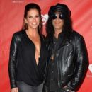 Musician Slash (R) and Perla Hudson attend the MusiCares MAP Fund Benefit Concert at Club Nokia on May 12, 2014 in Los Angeles, California. - 454 x 570