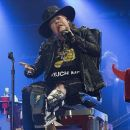 Put your feet up Axl! Rocker Rose puts on belting performance while confined to a chair as he joins AC/DC in Seville with his broken foot still in a cast - 454 x 380