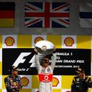Jenson Button of Great Britain and McLaren celebrates with the winner's as Sebastian Vettel of Germany and Red Bull Racing.finishing second (L) and Kimi Raikkonen of Finland and Lotus finishing third after the Belgian Grand Prix at the Circuit of Spa Fran