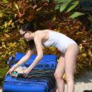Dakota Johnson in White Swimsuit at the pool in Miami
