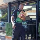 Lamar Odom heads back to an awaiting car and driver after grabbing some food to go in Los Angeles August 31, 2013