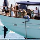 Queen's Roger Taylor uses a pole and shoots an AIRGUN at jellyfish whilst on a boat ride with his wife and children during sun-soaked holiday in Spain, 31 May 2019