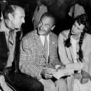 "Instructions for a scene in ""Springfield Rifle"" are given by Andre Toth, center, to Gary Cooper and Phyllis Thaxter, who star in the Western adventure"