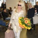 Pamela Anderson is greeted with flowers and a stretched limo upon her arrival at Vienna International Airport on March 5, 2012 in Vienna, Austria
