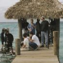 A behind the scenes shot of filming at the Atlantis Resort as Director Brett Ratner goes over the scene with Pierce Brosnan and Woody Harrelson while Boom Operator Mychal Smith and 1st A.D. Jamie Freitag stand by in New Line Cinema's film AFTER THE SU